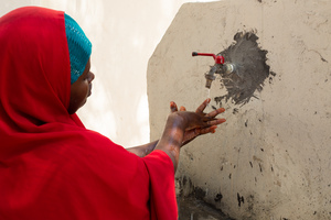 A_mother_washes_her_hands_at_a_handwashing_station_in_el_gaab_health_center_6_